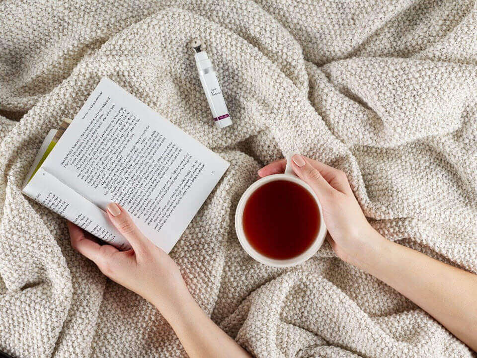 Hands in blanket with book, coffee and Dermalogica product | SalonCentric